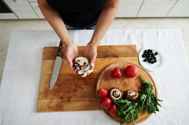 Vista dell'angolo alto del fungo affettato nelle mani femminili dello chef. ingredienti per la farcitura della pizza su tavola di legno nella cucina di casa