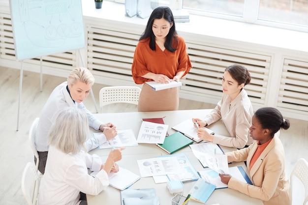 Vista di alto angolo alla donna di affari asiatica di successo che presenta il piano di progetto a un gruppo di colleghe mentre fa una pausa lavagna durante la riunione nella sala conferenze