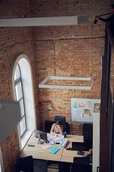 Vista dall'alto di una donna stanca con mal di testa che lavora su un nuovo progetto utilizzando un pc in un ufficio moderno