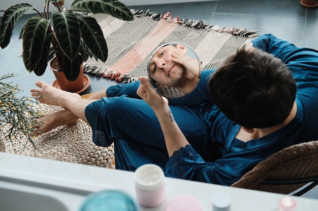 Veduta dall'alto del transgender in abito femminile che guarda lo specchio mentre è seduto in poltrona mentre fa una preparazione al mattino