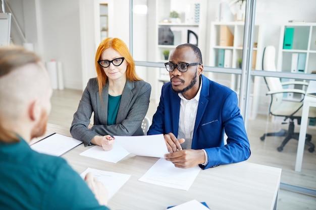 Veduta dall'alto a due responsabili delle risorse umane ascoltando il candidato durante il colloquio di lavoro in ufficio, copia dello spazio