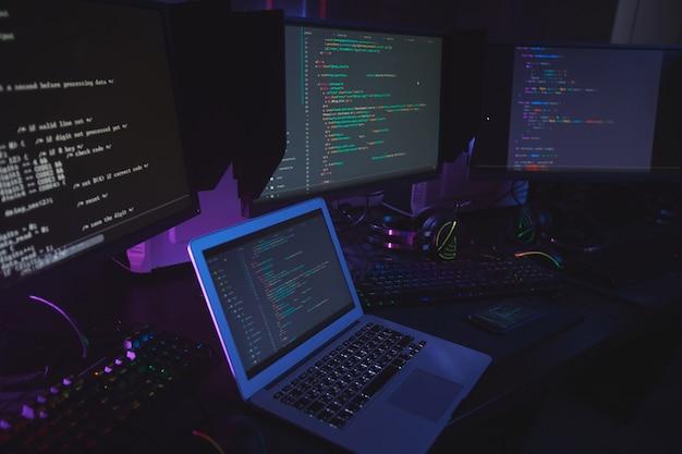 Veduta dall'alto a varie apparecchiature informatiche con codice di programmazione sugli schermi sul tavolo in camera oscura, concetto di sicurezza informatica, copia dello spazio