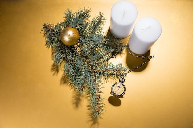 Elevato angolo di visione del pilastro bianco candele su sfondo giallo dorato con ramo sempreverde, sfera d'oro e antico orologio da tasca con spazio copia e illuminazione spot