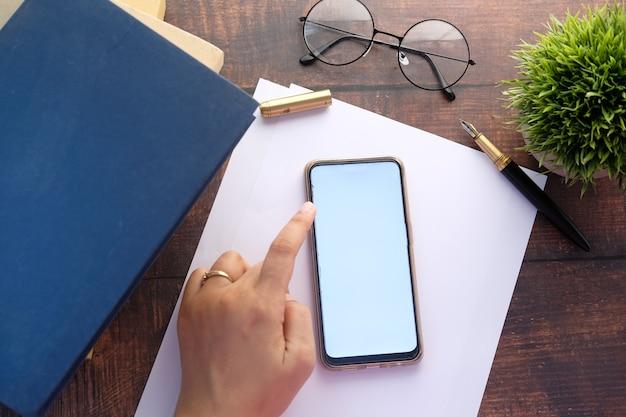 Elevato angolo di visione della mano delle donne utilizzando smart phone.