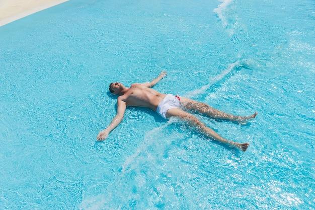 Vista di alto angolo di giovane uomo che indossa costume da bagno sdraiato sulla schiena con braccia e gambe divaricate in onde poco profonde della piscina in una giornata di sole in estate