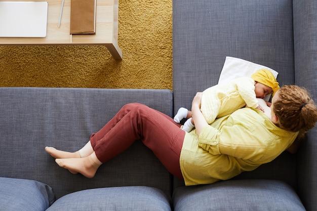 Veduta dall'alto di giovane madre sdraiata sul divano e allattamento al seno il suo bambino appena nato
