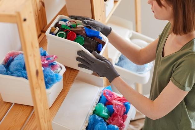 Vista di alto angolo alla giovane donna che ordina i rifiuti a casa, lo stoccaggio e il concetto di riciclaggio
