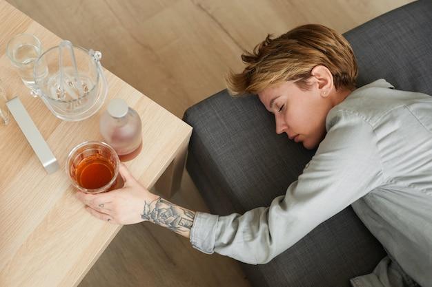 Vista di alto angolo della giovane donna con un bicchiere di whisky che dorme sul divano nella stanza che è ubriaca