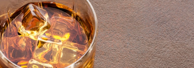Bicchiere da whisky ad alto angolo con ghiaccio e copia-spazio