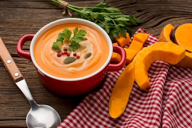 Alto angolo di zuppa di zucca invernale con prezzemolo e cucchiaio