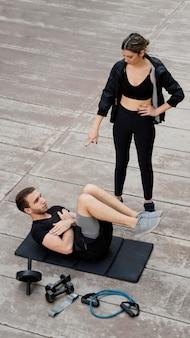 Elevato angolo di donna che aiuta l'uomo a fare esercizio all'aperto
