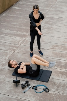 Alto angolo di donna che aiuta l'uomo ad allenarsi all'aperto