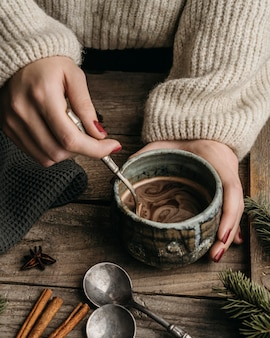 Tazza della holding della donna di alto angolo con cioccolata calda