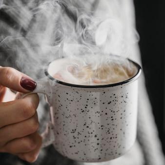 Tazza della holding della donna di alto angolo con la bevanda calda