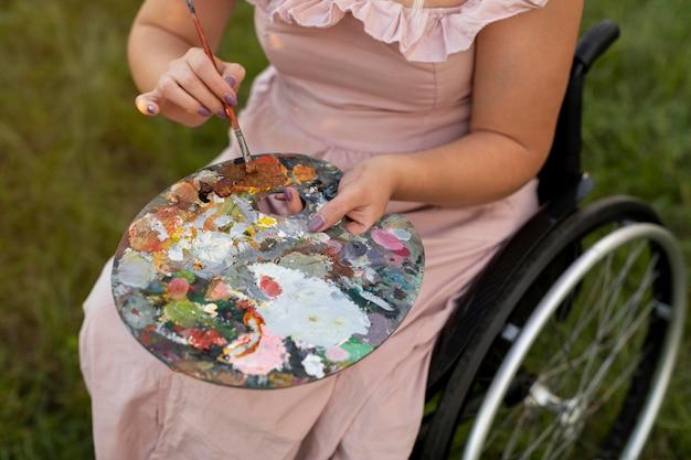 Alto angolo di donna in sedia a rotelle con tavolozza di vernice