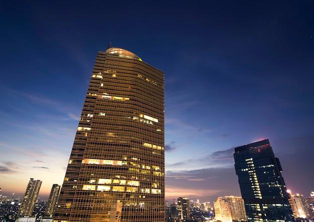 Un edificio alto con gente continua a lavorare di notte