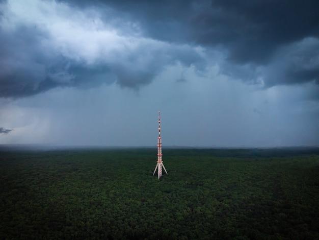 Alta antenna della torre di comunicazione nella vista aerea del drone della foresta