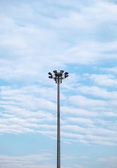 Palo elettrico alto e onda striata di nuvole su cielo blu