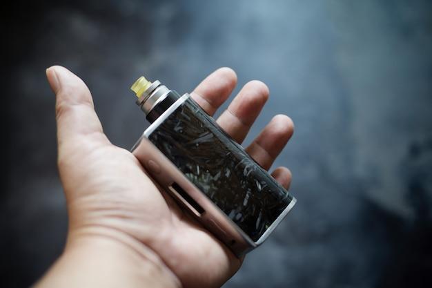 Fibra di carbonio nera di fascia alta in mod box regolati in resina trasparente con atomizzatore gocciolante ricostruibile e punta a goccia ultem in mano su sfondo grigio scuro, attrezzatura per vaporizzatore, messa a fuoco selettiva