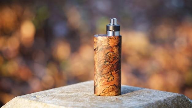 Mods scatola di legno stabilizzato naturale di fascia alta con atomizzatore gocciolante ricostruibile su sfondo texture bokeh, dispositivo di svapo, messa a fuoco selettiva