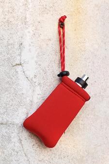 Atomizzatore di gocciolamento ricostruibile di fascia alta e mod box in sacchetto rosso appeso a una vecchia struttura di muro di cemento bianco, attrezzatura per vaporizzatore, fuoco selettivo