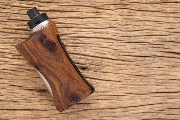 Atomizzatore gocciolante ricostruibile di fascia alta con mod box regolati in legno di noce stabilizzato naturale su sfondo rustico in legno naturale, attrezzatura per vaporizzatore
