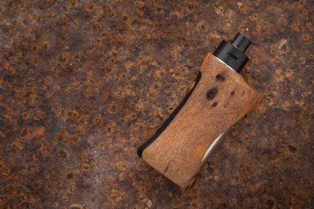 Atomizzatore gocciolante ricostruibile di fascia alta con mod box regolati in legno di noce stabilizzato naturale su sfondo texture arrugginito con spazio copia, attrezzatura per vaporizzatore