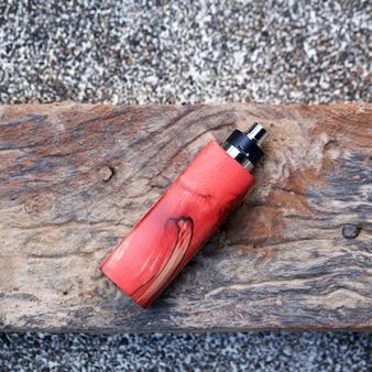 Mods scatola di legno stabilizzato naturale rosso di fascia alta con atomizzatore gocciolante ricostruibile su sfondo texture legno vecchio, dispositivo di svapo, messa a fuoco selettiva