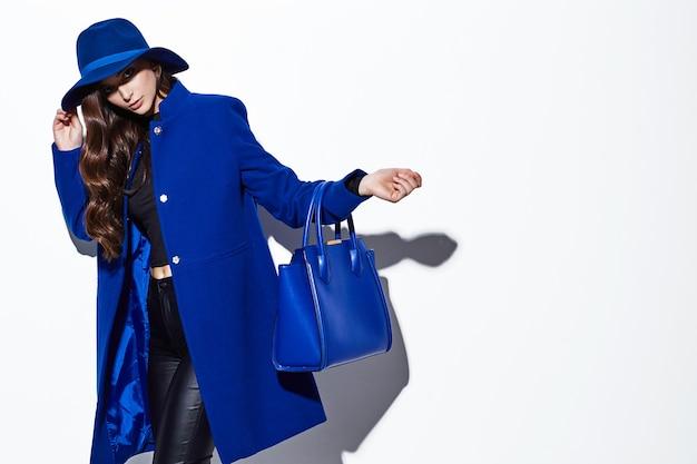 Alta moda ritratto di giovane donna elegante. cappotto blu, cappello, borsa. sfondo bianco
