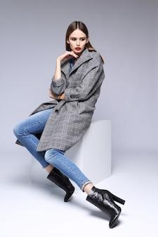 Alta moda ritratto di giovane donna elegante. grigio avena, salopette skinny in denim, stivaletti neri Foto Premium