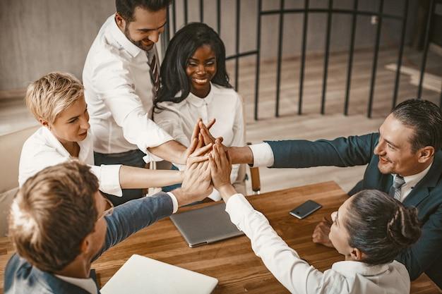 Il cinque dei colleghi di lavoro unisce le mani