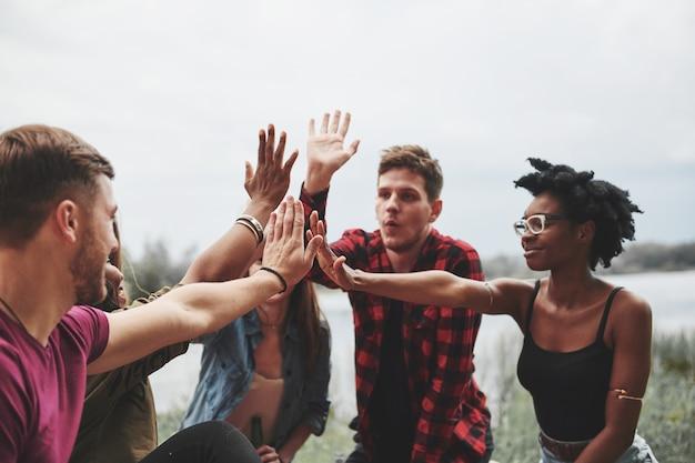 Batti il cinque a tutti. un gruppo di persone fa un picnic sulla spiaggia. gli amici si divertono durante il fine settimana.