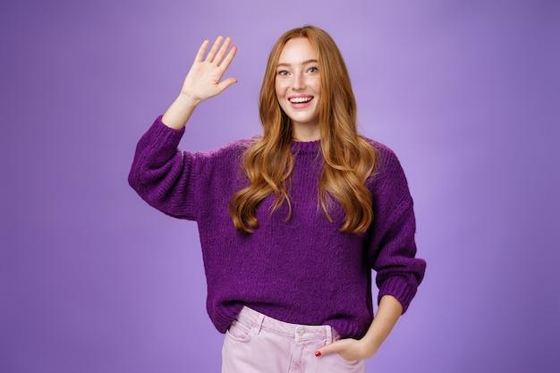 Batti il cinque amico, ciao. ritratto di amichevole ed eccitata ragazza rossa gentile affascinante in maglione alzando la mano e salutando in un gesto ciao, salutando il migliore amico e sorridendo ampiamente come soddisfatto dell'incontro.