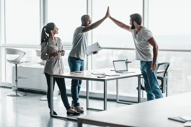 Batti il cinque per il successo foto di colleghi di lavoro entusiasti al chiuso di co-working. in piedi sul tavolo e darsi il cinque a vicenda.