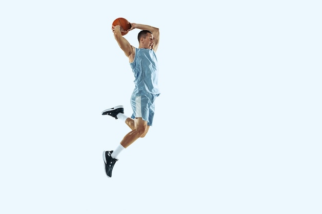 Volo alto giovane giocatore di basket caucasico della squadra in movimento d'azione nel salto isolato