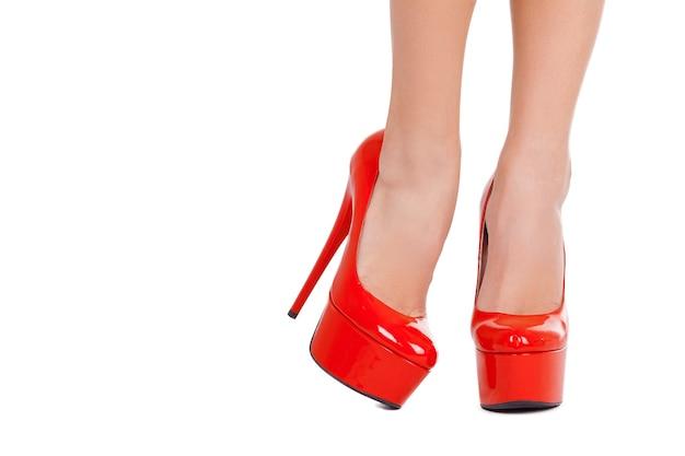 Eleganza con tacco alto. primo piano di belle gambe femminili in scarpe col tacco alto rosse isolate su fondo bianco