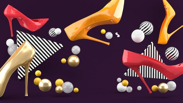 Scarpe col tacco in mezzo a palline colorate su uno spazio viola