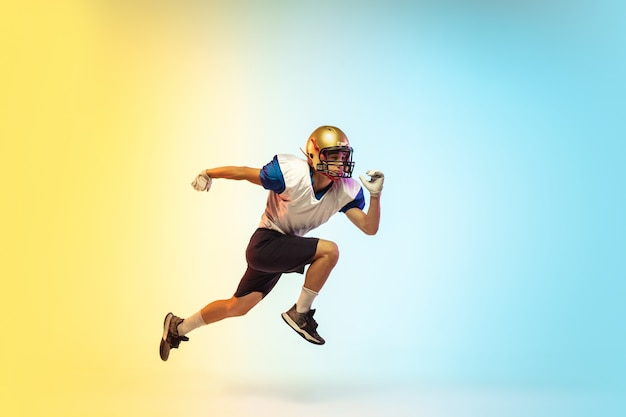 Salto in alto. giocatore di football americano isolato su gradiente in luce al neon