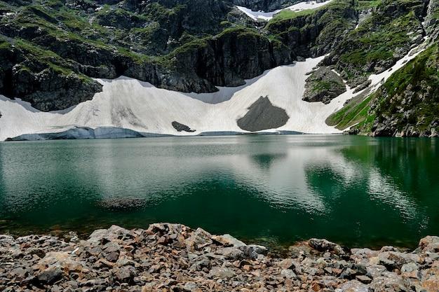 Lago di alta montagna con il primo piano dell'acqua turchese sullo sfondo delle montagne.