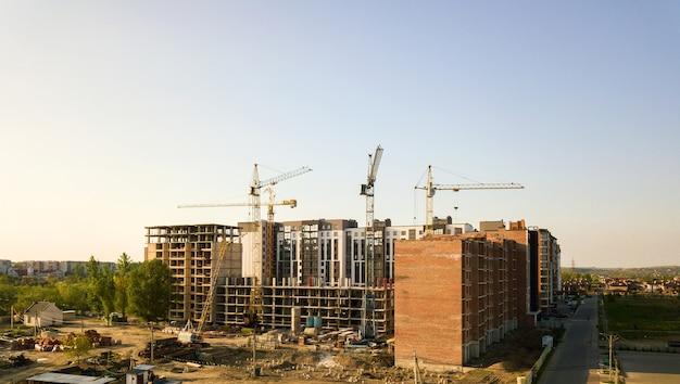Alti edifici residenziali multipiano in costruzione. incorniciatura in cemento e mattoni di un edificio alto. sviluppo immobiliare in area urbana.