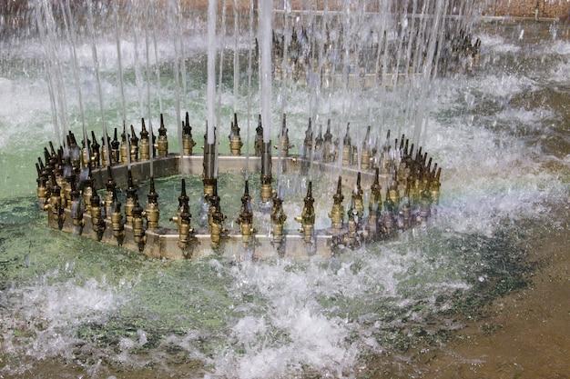 Ugelli metallici ad alta pressione su una fontana che spruzza getti d'acqua nell'aria in un display ornamentale, vista ravvicinata