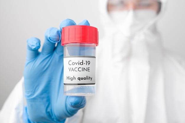 Flacone di vaccino covid 19 di alta qualità in mano ai medici. dottore in tuta protettiva, maschera facciale, sicurezza