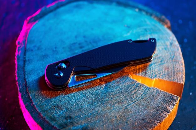 Coltello da tasca pieghevole moderno e di alta qualità, vista dall'alto su un supporto in legno. colore di sfondo di tendenza