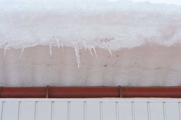 L'alto tetto di un edificio con un grande cumulo di neve. pericolo di caduta di neve dal tetto.