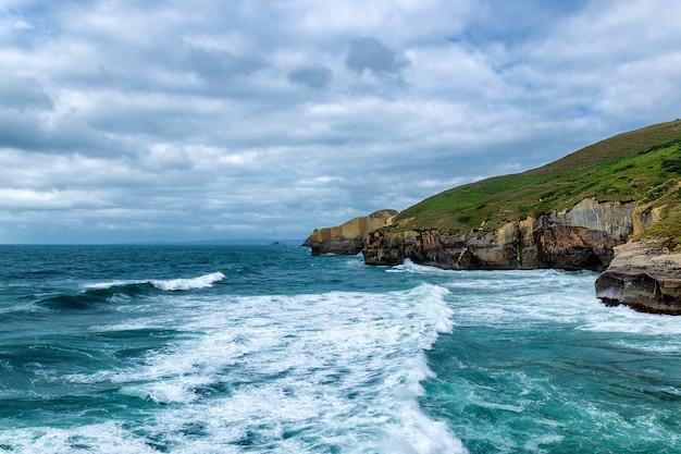 Le alte scogliere sabbiose e le onde dell'oceano pacifico al tunnel tirano, la nuova zelanda