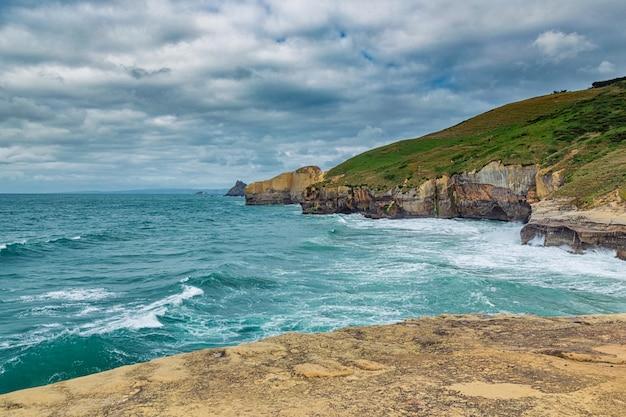 Alte scogliere sabbiose e onde dell'oceano pacifico a tunnel beach, nuova zelanda
