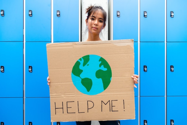 La ragazza del liceo che guarda la telecamera porta un aiutami a firmare con il disegno della sostenibilità della terra