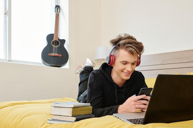 Studente di scuola superiore sdraiato sul letto con smartphone e messaggi di testo agli amici invece di prepararsi per gli esami