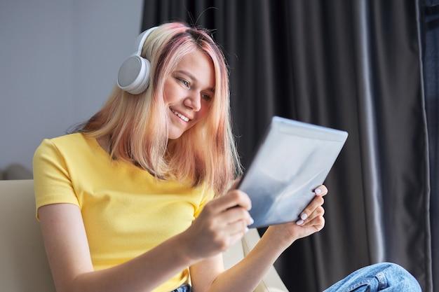 Ragazza adolescente studente di scuola superiore in cuffie con tablet a casa. studio di formazione online a distanza, blog e vlogging per il tempo libero guardando film, chat video con gli amici. stile di vita degli adolescenti