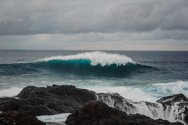 Onda di alto mare con schiuma e roccia nera sotto il cielo grigio nuvoloso in una giornata tempestosa